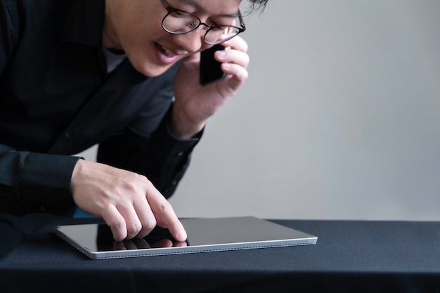 Imprenditore occupato facendo uso dello smartphone e della compressa digitale che fanno commercio elettronico, affare online con il concetto astuto di tecnologia