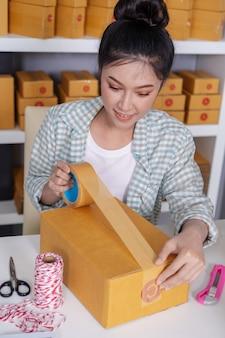 Imprenditore online della donna che utilizza nastro per imballare l'ufficio della cassetta dei pacchi a casa ufficio