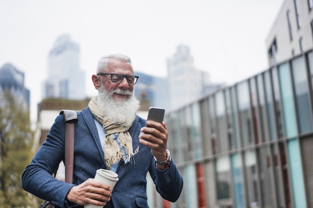 Imprenditore senior utilizzando il telefono cellulare mentre si va a lavorare