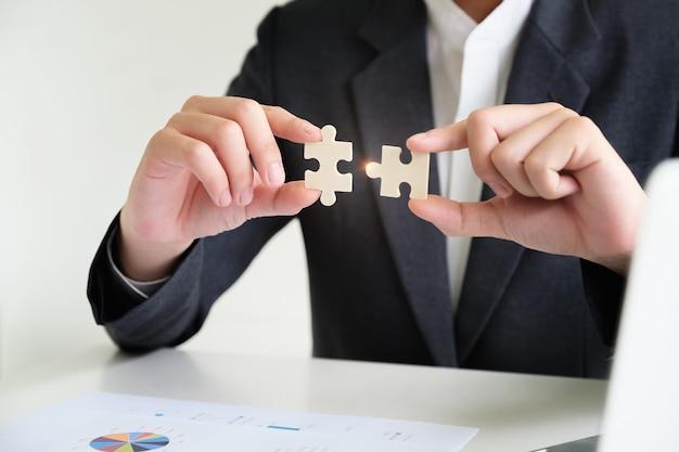 Imprenditore utilizzando due mani cercando di collegare coppia pezzo di puzzle, jigsaw da solo puzzle in legno contro.