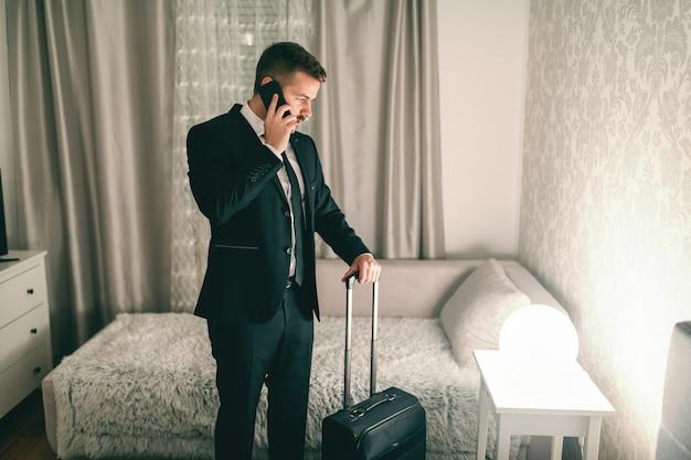 Imprenditore utilizzando smart phone stando in piedi in camera da letto e tenendo la valigia. concetto di viaggio d'affari.