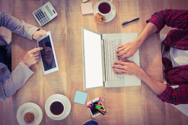 Imprenditori creativi che lavorano su dispositivi elettronici