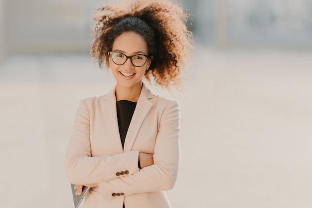 Imprenditrice allegra fiduciosa con i capelli ricci afro, tiene le braccia conserte, utilizza un moderno tablet computer