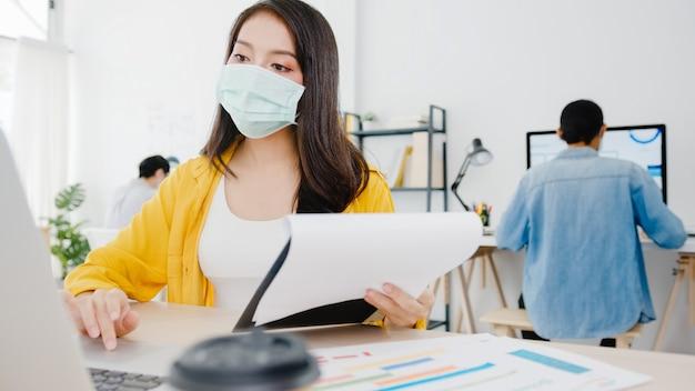 Imprenditrice asiatica imprenditrice indossando maschera medica per l'allontanamento sociale in una nuova situazione normale per la prevenzione dei virus mentre si utilizza il laptop al lavoro in ufficio. stile di vita dopo il virus corona.