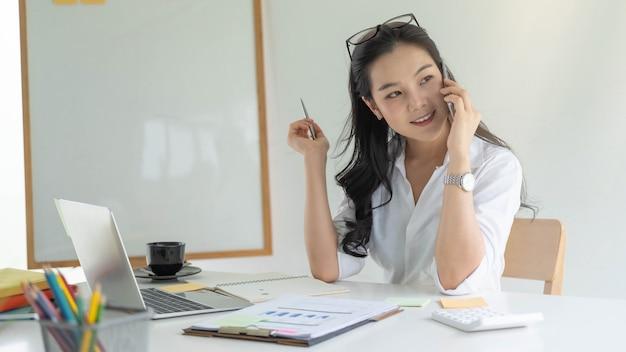 Imprenditrice che si siede nell'area di lavoro portatile durante la consulenza di chiamata