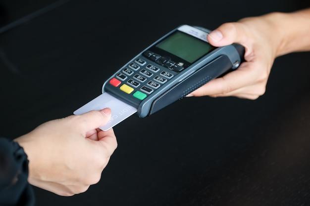 Imprenditrice che utilizza edc per ricevere la carta di credito per il pagamento dal cliente nel suo negozio.
