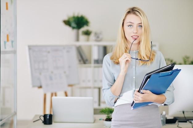 Imprenditrice con cartelle di documenti