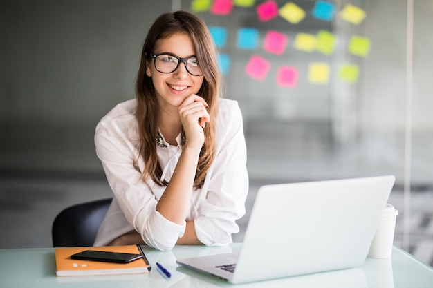 Imprenditrice di successo che lavora al computer portatile e pensa a nuove idee nel suo ufficio vestito con abiti bianchi