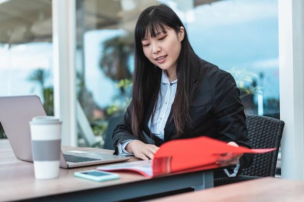 Imprenditrice donna asiatica che lavora e beve caffè all'interno dell'ufficio - business giovane femmina seduta alla sua scrivania nello spazio di coworking - tech e concetto di lavoro - focus sul volto di ragazza