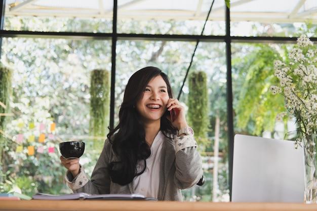 Imprenditrice parla sullo smart phone. donna di avvio che tiene tazza di caffè in ufficio.