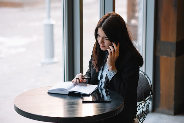 Imprenditrice parlando al telefono e prendendo appunti