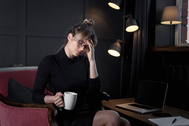 Imprenditrice professionale con mal di testa in ufficio