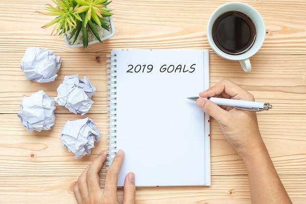 Imprenditrice scrivendo 2019 obiettivi con notebook, carta sbriciolata