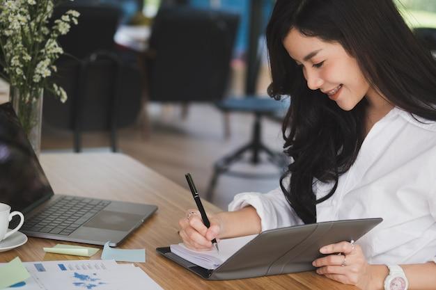 Imprenditrice scrivere nota sul notebook. donna che lavora con la relazione d'affari