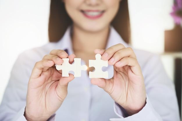 Imprenditrice utilizzando due mani cercando di collegare coppia pezzo di puzzle, jigsaw da solo puzzle in legno contro.