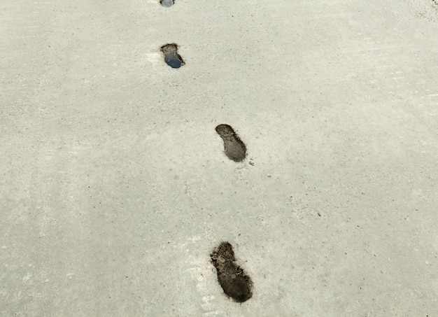 Impronta della scarpa sul fondo dell'estratto di superficie di calcestruzzo.
