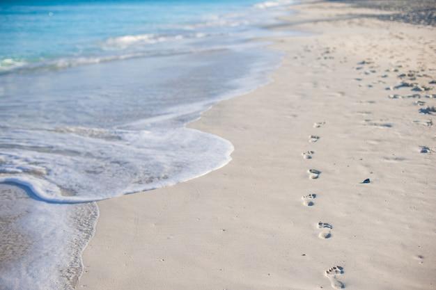 Impronte umane sulla spiaggia di sabbia bianca