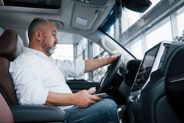 In attesa di una chiamata. l'uomo d'affari si siede nell'automobile moderna e ha alcuni affari