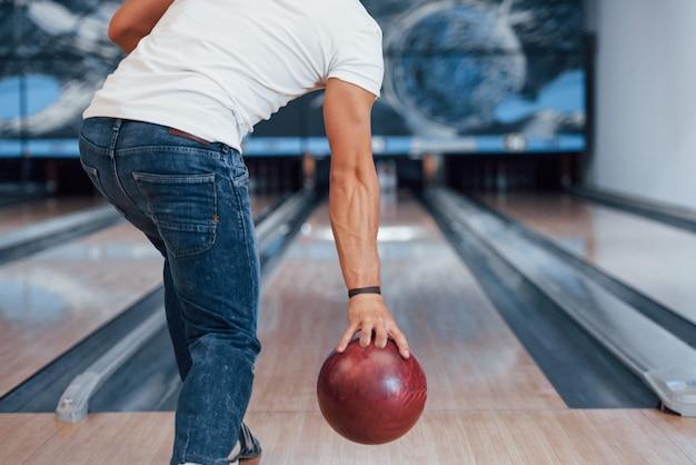 In camicia bianca e jeans. vista posteriore delle particelle dell'uomo in abiti casual che giocano a bowling nel club