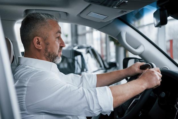 In camicia bianca e maniche arrotolate. uomo d'affari senior in vestiti ufficiali che provano nuova automobile di lusso in salone automatico