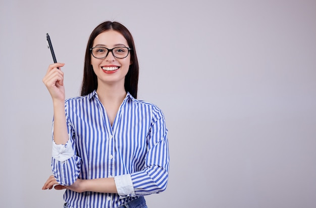 In è una piacevole giovane donna d'affari sorridente con i capelli e gli occhiali castani. la donna tiene in mano una penna nera.