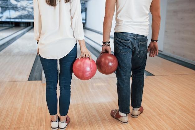 In jeans e camicie bianche. vista ritagliata di persone al bowling pronte a divertirsi