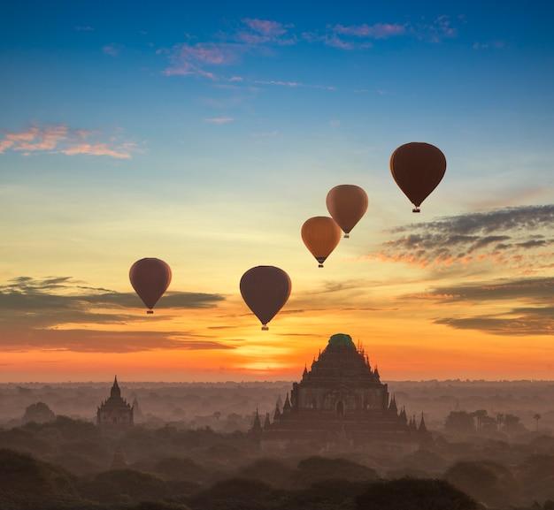 In mongolfiera ad aria calda sulla pianura di bagan nella nebbiosa mattina, myanmar all'alba.