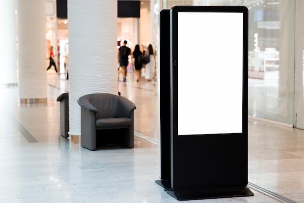In piedi cartellone bianco all'interno del centro commerciale