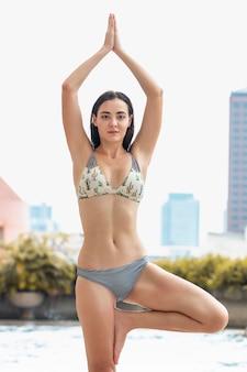 In pioggia. giovane bella donna caucasica in bikini praticando yoga vicino alla piscina.