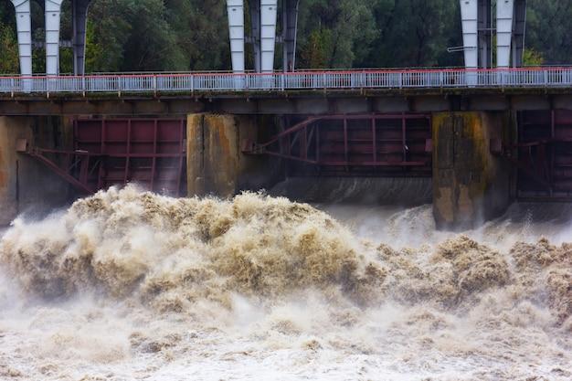 In primavera scorre veloce corrente di acqua sporca alla diga