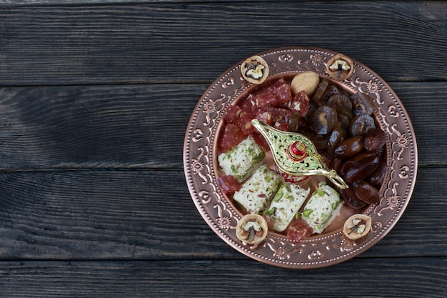 In un piatto di bronzo datteri, noci, halva, delizia turca e noci