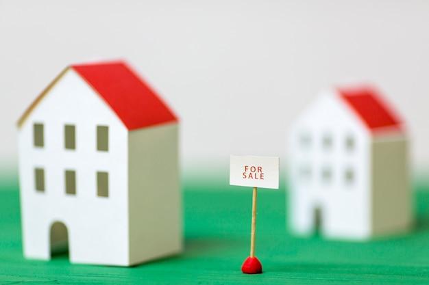 In vendita post vicino al modello di casa sfocato sulla scrivania verde