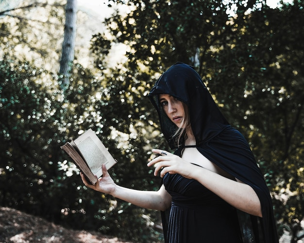 Incantatrice con libro degli incantesimi nei boschi assolati