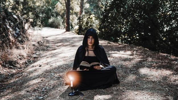 Incantatrice femminile con il libro e il candeliere che si siedono sul sentiero nel bosco