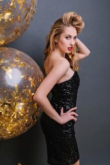 Incantevole ragazza bionda che guarda sopra la spalla e gioca con i suoi capelli durante il servizio fotografico della festa. slim bionda signora indossa un abito nero in posa con palloncini dorati.