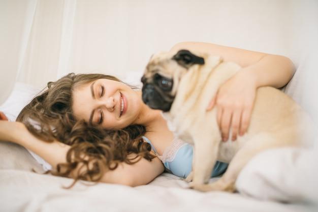 Incantevole weekend in famiglia. donna che si rilassa a letto con il cane del carlino