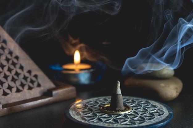 Incenso aromatico accanto a una candela accesa