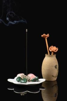 Incenso con elefante e pietre e vaso in ceramica su fondo nero