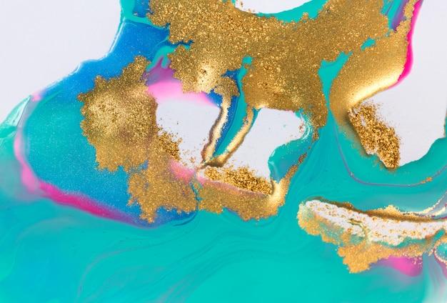 Inchiostri misti oro e blu schizzati su carta bianca sullo sfondo.