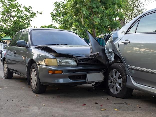 Incidente stradale in strada con relitto e automobili danneggiate.