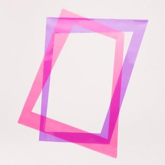 Inclinare la cornice viola e rosa su sfondo bianco