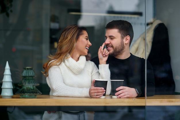 Incontri in un caffè. bella ragazza sorridente con il suo ragazzo seduto in un caffè godendo nel caffè e nella conversazione.