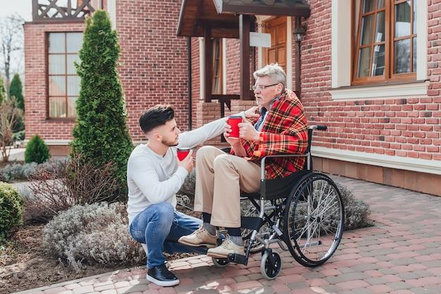 Incontro di famiglia! figlio con suo padre tenendo caffè e parlando con papà