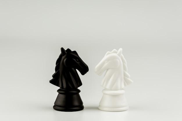 Incontro di scacchi in bianco e nero a cavallo. - vincitore del business e concetto di combattimento.