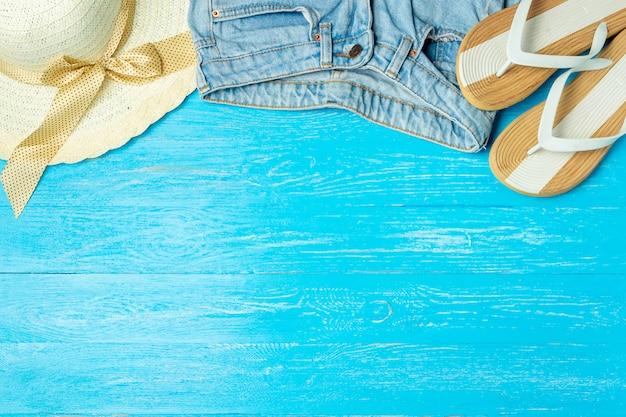 Incornici i jeans femminili eleganti delle pantofole del cappello di paglia su fondo di legno blu, il copyspace, vacanze estive.