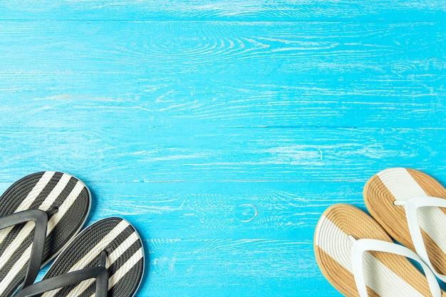 Incornicia le pantofole femminili eleganti su fondo di legno blu, copyspace, vacanze estive.