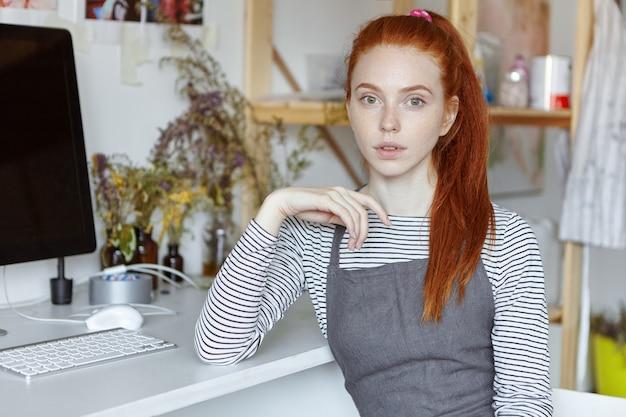 Incredibile artista femminile professionista con lentiggini e lunghi capelli di zenzero seduto al computer sul tavolo bianco nel suo laboratorio moderno, con uno sguardo pensieroso, profondo nei pensieri, assorbito da idee creative