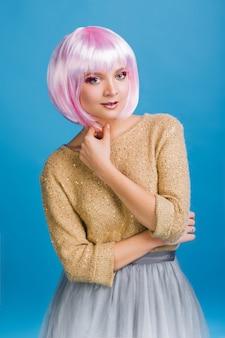 Incredibile bella giovane donna con i capelli rosa tagliati. maglione dorato, gonna in tulle grigio, trucco da festa, emozioni vere, festa, compleanno.