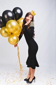 Incredibile donna alla moda allegra in abito da sera nero di lusso e corona gialla sulla testa per celebrare il nuovo anno, sorridente e con palloncini gialli e neri, labbra rosse, faccia sorpresa di emozione.