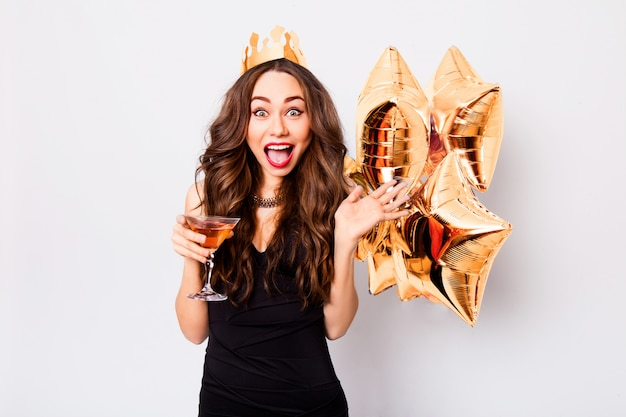 Incredibile donna elegante allegra in abito da sera nero che celebra il nuovo anno, sorridendo e tenendo in mano un bicchiere di champagne, labbra rosse, stelle d'oro palloncino, emozione sorpresa.